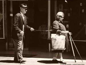 En seende kvinne leder en blind mann i bånd